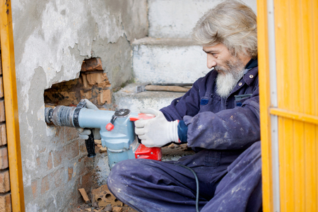 making hole: worker with pneumatic hammer drill perforator equipment making hole in wall at construction site
