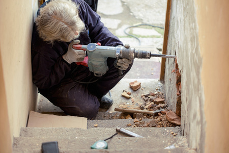 making hole: Builder worker with pneumatic hammer drill perforator equipment making hole in wall at construction site Stock Photo