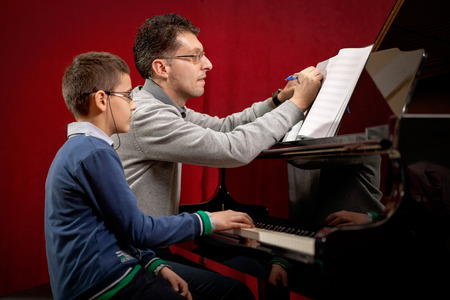 teaches: father teaches his young son playing piano Stock Photo