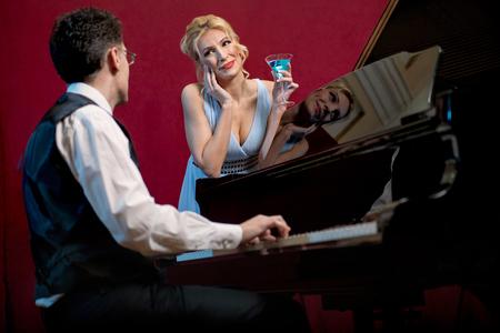 piano player: piano player plays piano, lady enjoys Stock Photo