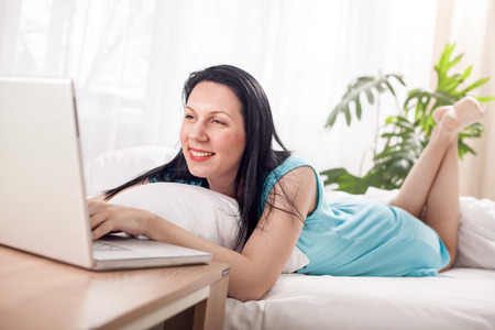 legs crossed on knee: Beautiful young woman relaxing on her bed , working with her laptop Stock Photo