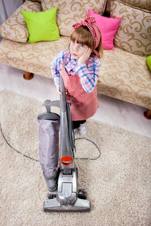 aide: little girl cleaning the room - using vacuum cleaner Stock Photo