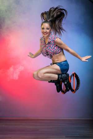 Sourire fille brune aux cheveux longs de sauter dans kangoo sauts chaussures