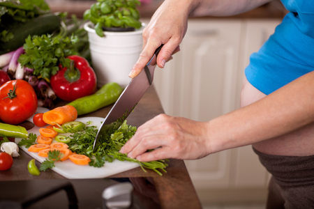 Pregnant woman preparing a healthy meal in the kitchen photo