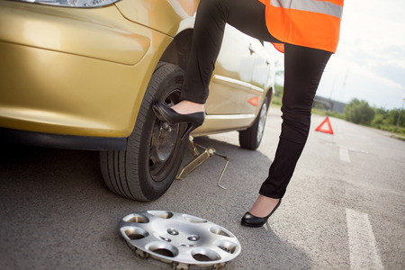 hubcap: woman changing the broken Tire