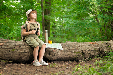 summer nature: excited little girl on a camping trip in green forest Stock Photo