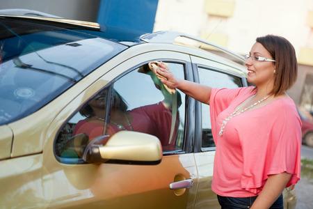 washing car: attractive woman washing car window Stock Photo