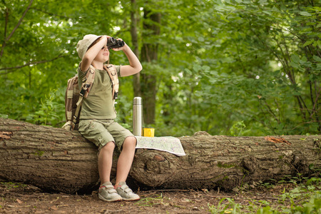 excited little girl on a camping trip in green forest Foto de archivo