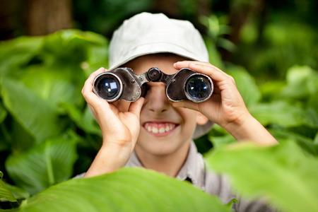 Boy hiding in grass looking through binoculars outdoor Stock Photo