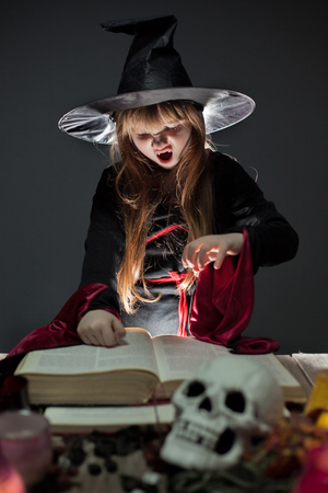 Little cute halloween witch reading spell