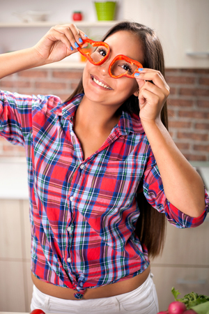 girl holding slices of yellow bell pepper in front of his eyes