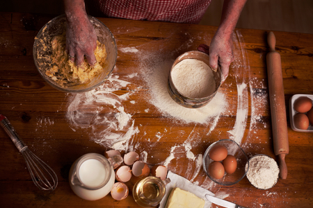 sifter: Baking ingredients for cookies.woman hands sifter flour