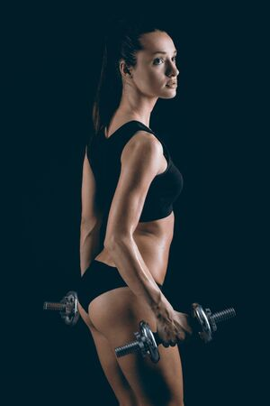 Bodybuilding.. Muscular young girl lifting weights on black