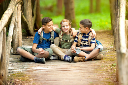 Young scouts sitting on old wooden bridge in the woods