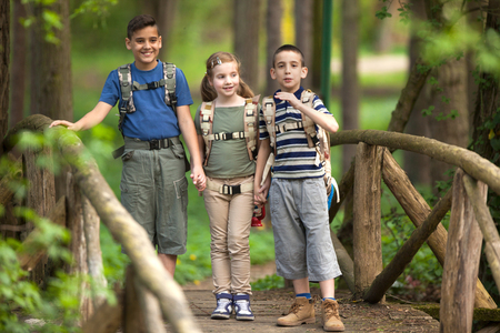 scouting: boys and girl go hiking with backpacks on forest road