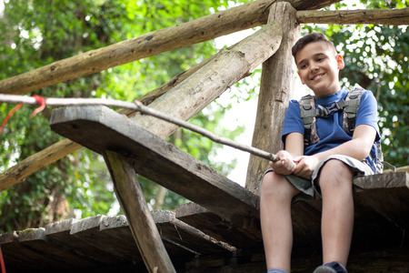 happynes: kid scout on old wooden bridge in forest