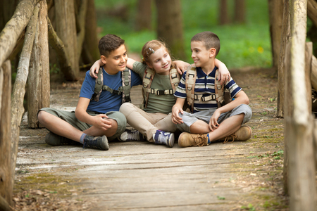 happynes: Young scouts sitting on old wooden bridge in the woods