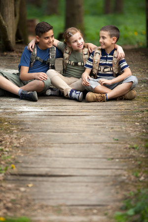 happynes: Young scouts sitting on old wooden road in forest