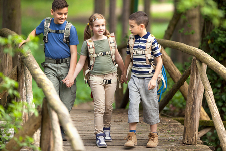 happynes: boys and girl go hiking with backpacks on forest road