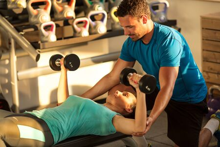 Gym,womanlifting dumbbells with assisting her personal trainer