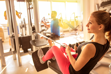 Woman exercising with crossover in fitness club or gym training legs