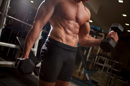 Muscular bodybuilder guy doing exercises with dumbbells in gym Banque d'images