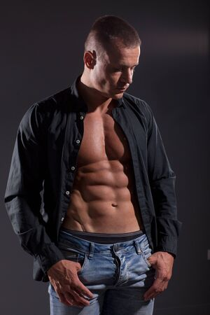 Fitness  Male Model posing near dark gray wall Banque d'images
