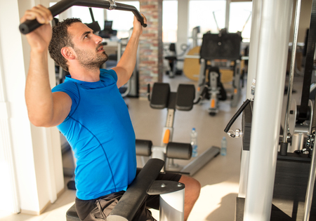 Sport, fitness, lifestyle, technology and people concept. Young man training in the gym Banque d'images