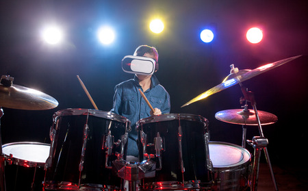 young boy playing drums  using viewer for virtual reality