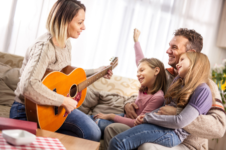 Adult woman playing guitar for child girl  and hubby indoors