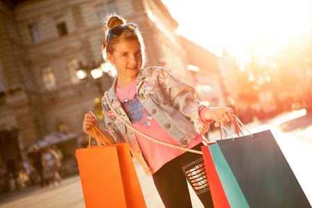 Jeune fille à la rue avec des sacs à provisions