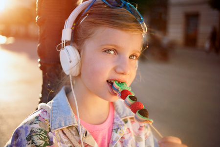Young beautiful child girl with headphones