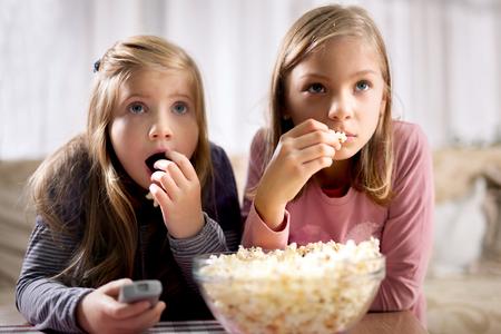 Deux jeunes filles belles manger du maïs soufflé et regarder des films Banque d'images