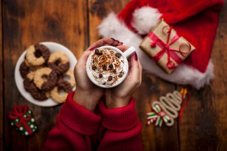 Young woman hands holding cup of coffee with christmas gifts Banque d'images
