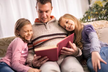 Little girls and father are enjoying reading book together