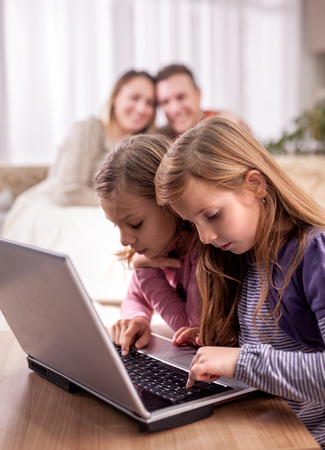 two smiling sister with tablet pc computer and parents on the back with laptop