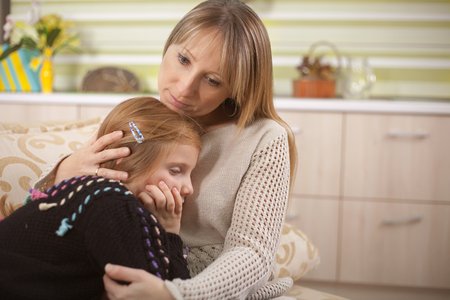 Mother comforts her troubled  daughter