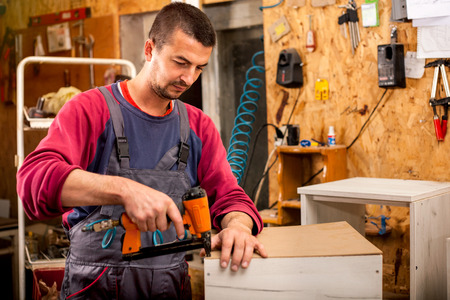 Man collects furniture uses a professional stapler or nail gun