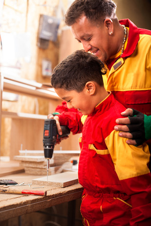 father and little son with drill perforating wood plank at workshop