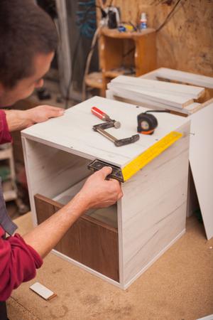 carpenter  with yardstick in workshop