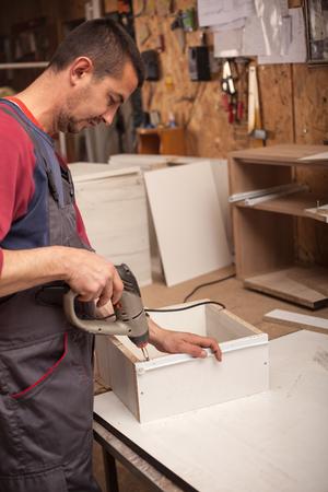 Carpenter drilling wooden board in workshop Banque d'images