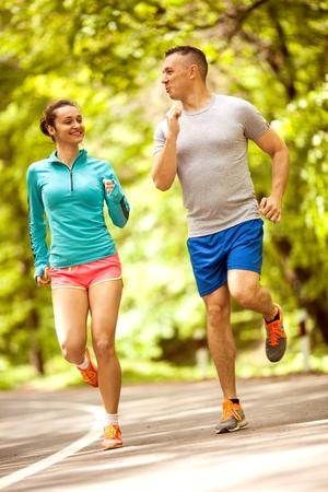 Jeune couple, faire du jogging dans les bois Banque d'images