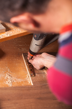Carpenter drilling wooden board in workshop Stock Photo
