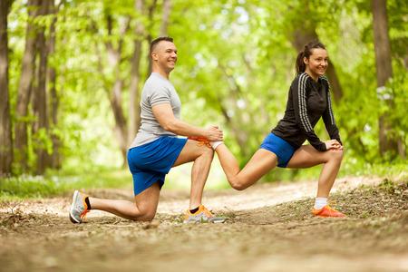 Concept de conditionnement physique, de sport, d'amitié et de mode de vie - couple souriant execirse dans la forêt verte