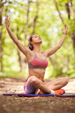 Beautiful sport woman practicing yoga in the forrest