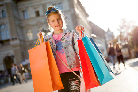 Young happy modern gir having fun with shopping bags on streeet