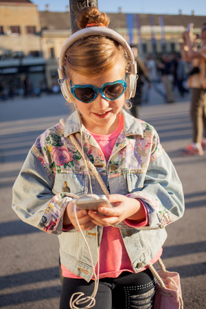 Pretty  young girl listening music with her headphones in the street Banque d'images