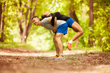 fitness, sport, friendship and lifestyle concept - smiling couple execirse in green forest