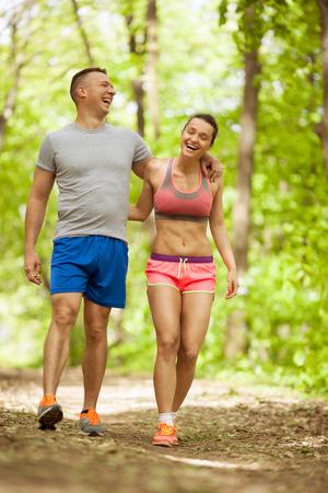 Embrasser jeune couple sportif dans la forêt