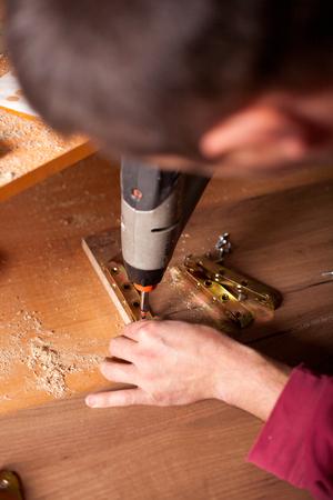 Menuisier de forage de planche de bois dans l'atelier